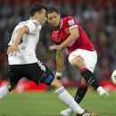 This is a Tuesday Aug. 12, 2014 file photo of Manchester United's Javier Hernandez as he fires a shot past Valencia's Javi Fuego during a pre season friendly soccer match at Old Trafford Stadium, Manchester, England. Real Madrid has signed Mexico stri