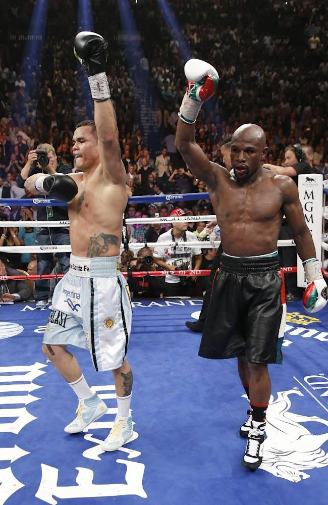 Floyd Mayweather Jr., right, and Marcos Maidana, from Argentina, both react at the end of their WBC-WBA welterweight title boxing fight Saturday, May 3, 2014, in Las Vegas. Mayweather won the bout by majority decision