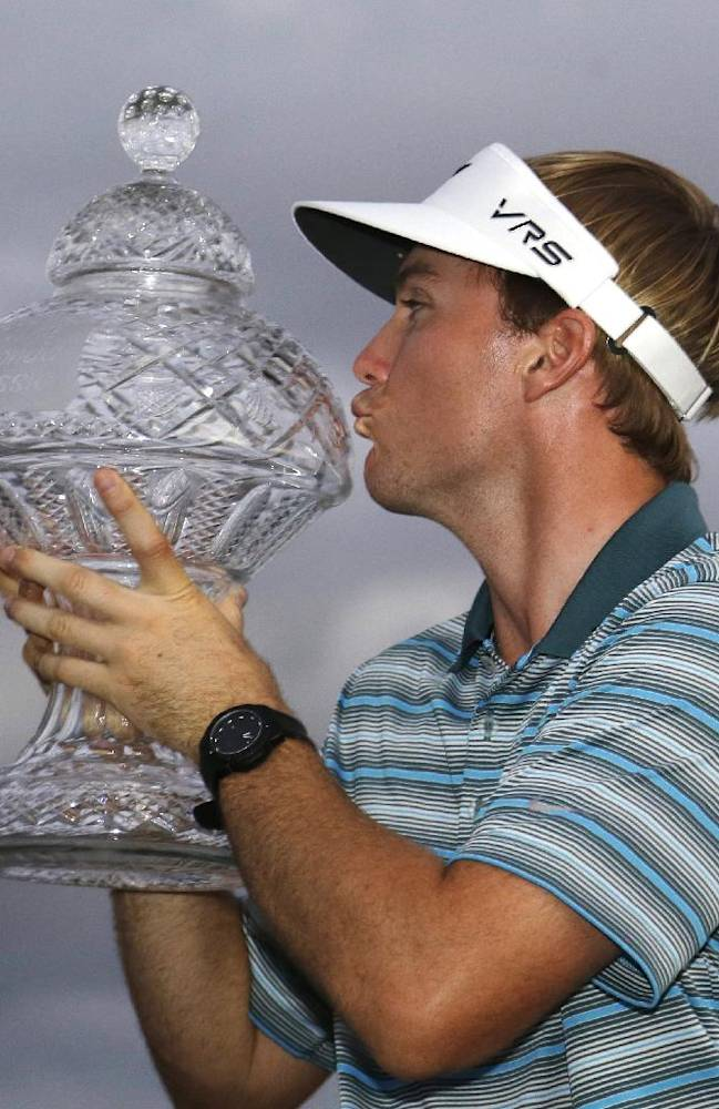 Russell Henley kisses the trophy after winning the Honda Classic golf tournament, Sunday, March 2, 2014 in Palm Beach Gardens, Fla
