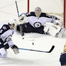 Winnipeg Jets goalie Ondrej Pavelec (31), of the Czech Republic, blocks the shot of Nashville Predators forward Mike Fisher (12) as defenseman Mark Stuart (5) tries to clear the puck in the third period of an NHL hockey game on Saturday, March 1, 2014, in