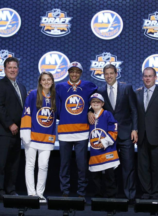 Joshua Ho-Sang stands with New York Islanders officials after being chosen 28th overall during the first round of the NHL hockey draft, Friday, June 27, 2014, in Philadelphia