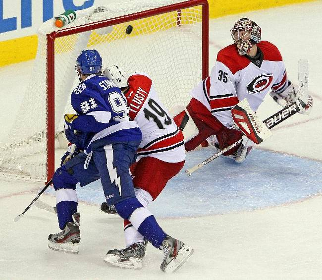 Tampa Bay Lightning's Steven Stamkos (91) beats Carolina Hurricanes' Jiri Tlusty (19) of the Czech Republic, to net the puck behind goalie Justin Peters (35) during the third period of an NHL hockey game in Raleigh, N.C., Friday, Nov. 1, 2013.  Lightning won 3-0