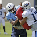 Tennessee Titans wide receivers coach Shawn Jefferson, center, wears a helmet, pads and a jersey as he serves as a blocker as wide receiver Brian Robiskie (17) and other players go through a drill during NFL football training camp Tuesday, July 29, 2014,