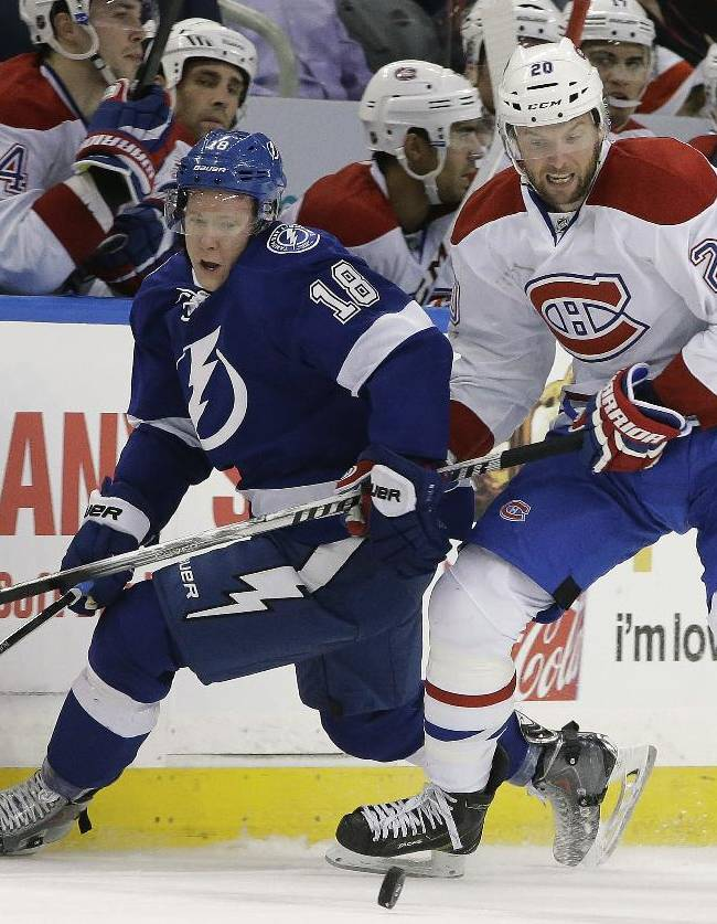 Montreal Canadiens left wing Thomas Vanek (20), of Austria, knocks Tampa Bay Lightning left wing Ondrej Palat, of the Czech Republic, off the puck during the second period of an NHL hockey game Tuesday, April 1, 2014, in Tampa, Fla