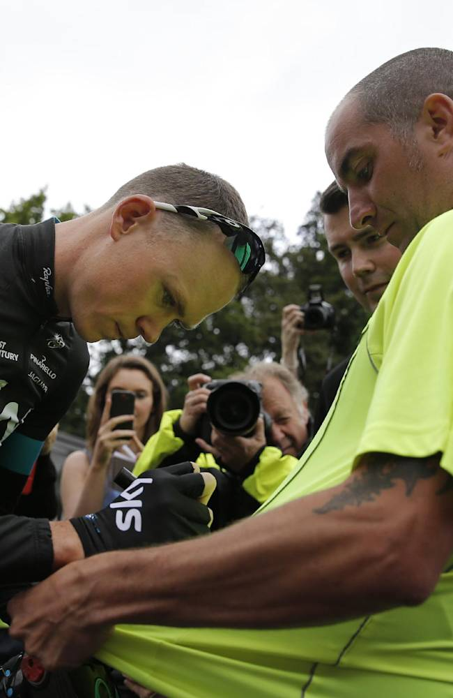 Britain's Christopher Froome autographs a jersey od a fan when leaving for a training ahead of the Tour de France cycling race in Leeds, Britain, Thursday, July 3, 2014. The Tour de France will start on Saturday July 5th in Leeds, and finishes in Paris on Sunday July 27th