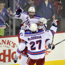 New York Rangers' Kevin Klein celebrates his game-winning goal in overtime with Ryan McDonagh (27) and Derick Brassard (16) during an NHL hockey game against the New Jersey Devils Tuesday, Oct. 21, 2014, in Newark, N.J. The Rangers won 4-3. (AP Photo/Bill Kostroun)
