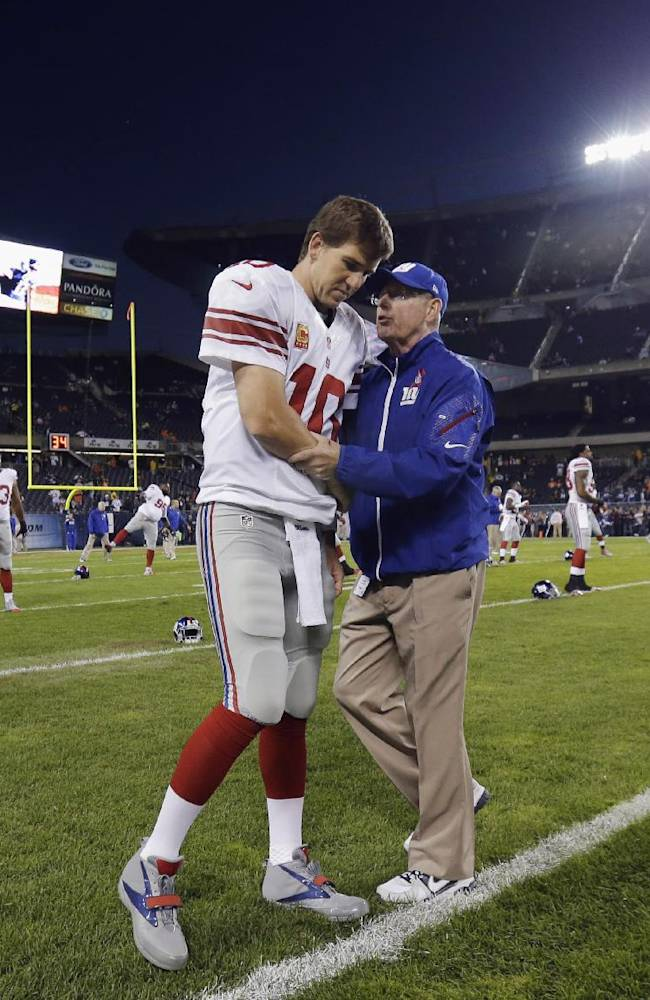 New York Giants coach Tom Coughlin talks to quarterback Eli Manning before the Giants' NFL football game against the Chicago Bears, Thursday, Oct. 10, 2013, in Chicago
