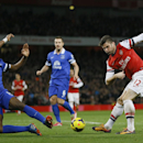 Arsenal's Olivier Giroud, right, shoots at goal as Everton's Sylvain Distin tempts to block during the English Premier League soccer match between Arsenal and Everton at the Emirates Stadium in London, Sunday, Dec. 8, 2013