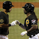 Pittsburgh Pirates' Andrew McCutchen, right, is greeted by teammate Pedro Alvarez as he returns to the dugout after hitting a solo home run off Cincinnati Reds starting pitcher Johnny Cueto during the ninth inning of a baseball game in Pittsburgh Tuesday,