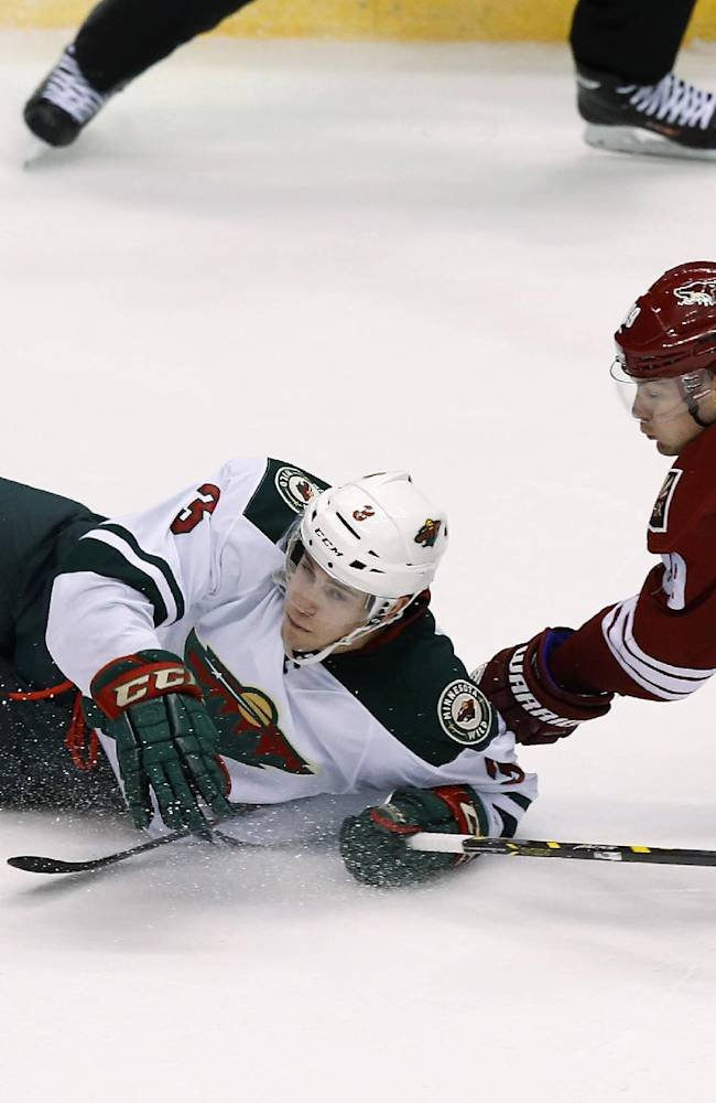 Minnesota Wild's Charlie Coyle (3) gets tripped up by Phoenix Coyotes' Mikkel Boedker (89), of Denmark, during the third period of an NHL hockey game, Saturday, March 29, 2014, in Glendale, Ariz. The Wild defeated the Coyotes 3-1