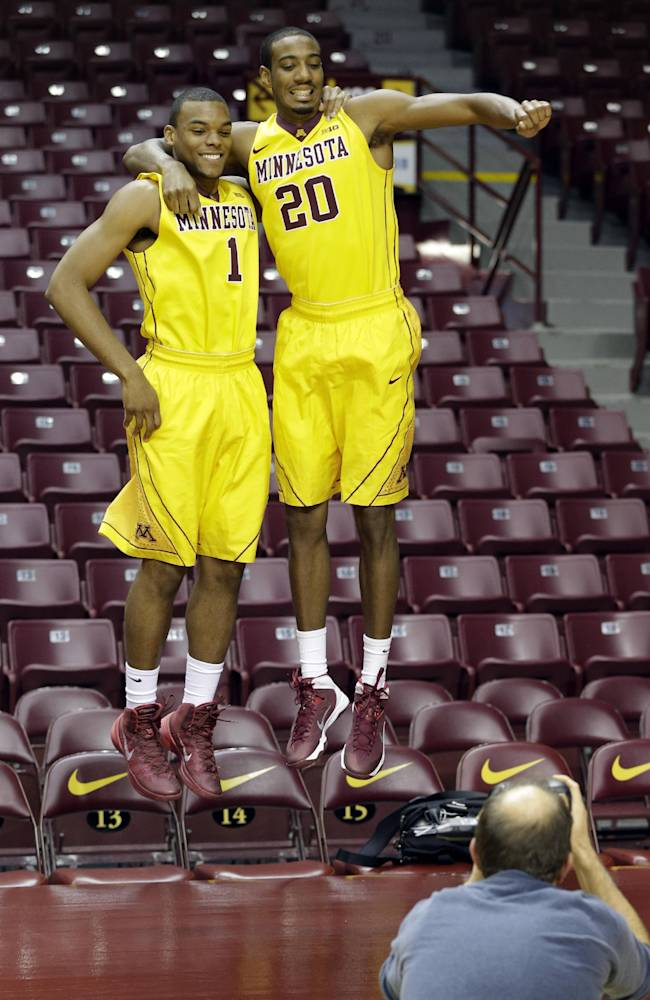 Minnesota basketball players Andre Hollins, left, and Austin Hollins (no relation) do a double jump for a photographer on media day, Monday, Oct. 28, 2013, in Minneapolis