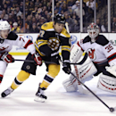 Boston Bruins left wing Milan Lucic (17) skates between New Jersey Devils goalie Cory Schneider (35) and defenseman Jon Merrill (7) during the second period of an NHL hockey game in Boston, Thursday, Jan. 8, 2015 The Associated Press