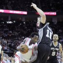Houston Rockets' Patrick Beverley, left, drives past San Antonio Spurs' Aron Baynes (16) as Tony Parker (9) looks on in the first half of an NBA basketball game Monday, April 14, 2014, in Houston The Associated Press