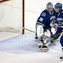 Vancouver Canucks defenseman Chris Tanev (8) looks on as Arizona Coyotes center Antoine Vermette's shot goes past Vancouver Canucks goalie Ryan Miller (30) during the second period of an NHL hockey game in Vancouver, British Columbia, Monday, Sept. 29, 20