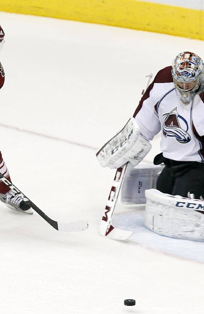 Colorado Avalanche's Semyon Varlamov, right, of Russia, makes a save on a shot by Phoenix Coyotes' Tim Kennedy (34) during the first period of an NHL hockey game Thursday, Nov. 21, 2013, in Glendale, Ariz