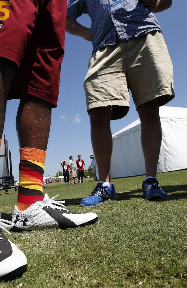 Washington Redskins safety Ryan Clark wears multi-colored socks as he speaks with the media after practice at the team's NFL football training facility, Friday, July 25, 2014 in Richmond, Va. (AP Photo)