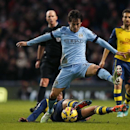 Manchester City's David Silva leaps over a tackle by Arsenal's Francis Coquelinduring the English Premier League soccer match between Manchester City and Arsenal at the Etihad Stadium, Manchester, England, Sunday, Jan. 18, 2015