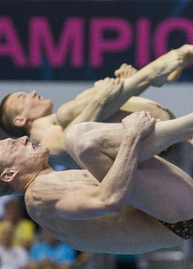 Russia's Ilia Zakharov, front, and Evgenii Kuznetsov compete during the men's synchronized 3m springboard diving final at the LEN Swimming European Championships in Berlin, Germany, Friday, Aug. 22, 2014