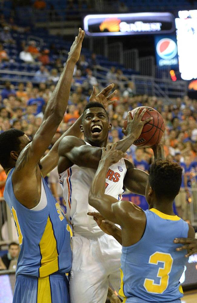 Florida forward Casey Prather, center, is sandwiched by southern University guard YonDarius Johnson  and southern University guard Trelun Banks (3) during the first half of an NCAA college basketball game Monday, Nov. 18, 2013, in Gainesville, Fla