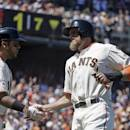San Francisco Giants' Hunter Pence, right, is greeted by teammate Hector Sanchez, left, after scoring the Giants' second run in the seventh inning of their baseball game against the Milwaukee Brewers, Wednesday, July 29, 2015, in San Francisco. (AP Photo/Eric Risberg)