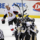 Pittsburgh Penguins' Christian Ehrhoff (10) is mobbed by teammates as they celebrate his goal late in the third period of an NHL hockey game as Ottawa Senators' Marc Methot (3) heads back to his bench in Pittsburgh, Saturday, Dec. 6, 2014. The Penguins wo