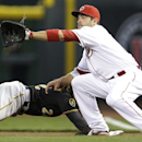 Pittsburgh Pirates' Andrew McCutchen dives safely back to first as Cincinnati Reds first baseman Joey Votto catches a pickoff throw in the first inning of a baseball game, Monday, April 14, 2014, in Cincinnati The Associated Press