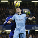 Chelsea's Kurt Zouma, left, jumps for the ball with Manchester City's James Milner during the English Premier League soccer match between Chelsea and Manchester City at Stamford Bridge stadium in London, Saturday, Jan. 31, 2015