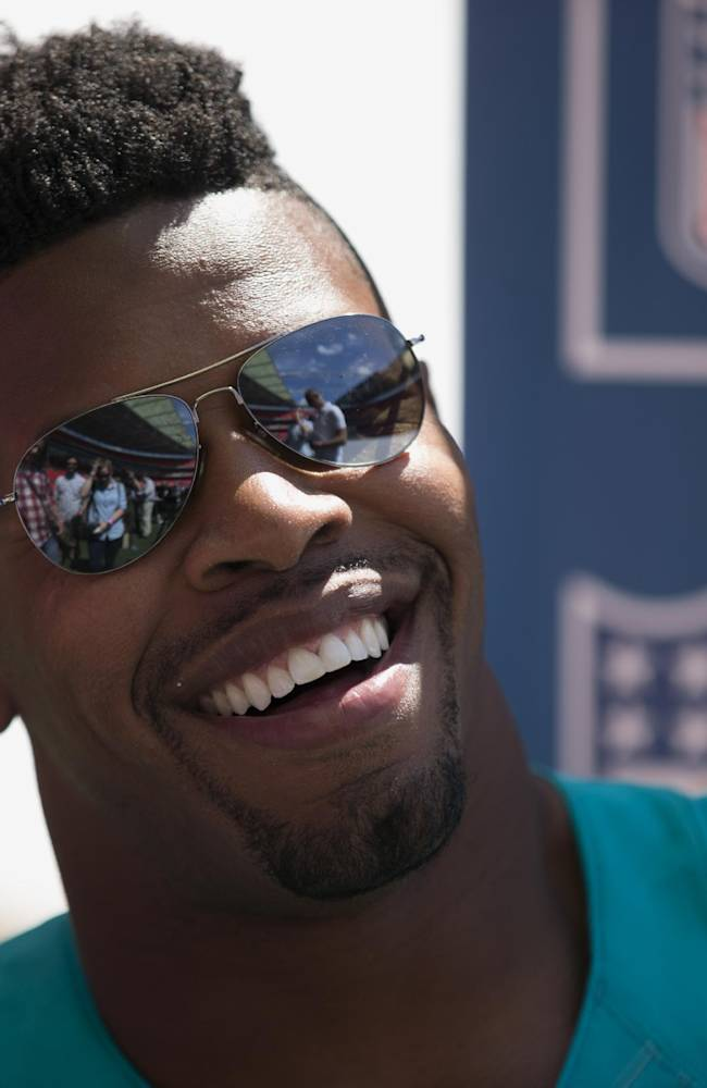 NFL player Miami Dolphins defensive end Cameron Wake laughs as he gives a media interview at Wembley Stadium in London, Wednesday, July 16, 2014. Six players from teams who will play in the three regular season NFL games at Wembley in the autumn were in London for media and promotional events on Wednesday