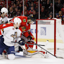 Chicago Blackhawks center Michal Handzus (26) reaches in to score a goal past Florida Panthers goalie Scott Clemmensen (30) and defenseman Dylan Olsen (4) during the second period of an NHL hockey game on Sunday, Dec. 8, 2013, in Chicago, Ill The Associat