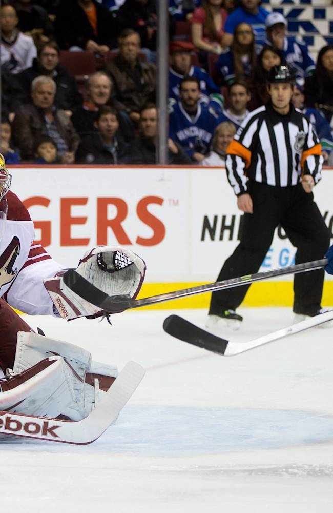 Phoenix Coyotes goalie Mike Smith, left, makes the save as Vancouver Canucks' Brad Richardson redirects the puck during first period NHL hockey game in Vancouver, British Columbia, on Sunday, Jan. 26, 2014