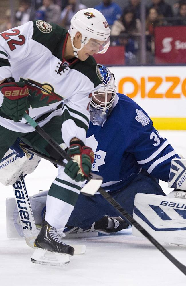 Toronto Maple Leafs goaltender James Reimer makes a save on Minnesota Wild right winger Nino Niederreiter (22) as defenseman Dion Phaneuf (3) helps Reimer during the first period of an NHL hockey game in Toronto on Tuesday, Oct. 15, 2013