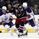Columbus Blue Jackets' Blake Comeau (14) works for the puck between Edmonton Oilers' Sam Gagner (89) and Nick Schultz (15) in the first period of an NHL hockey game in Columbus, Ohio, Friday, Nov. 29, 2013 The Associated Press