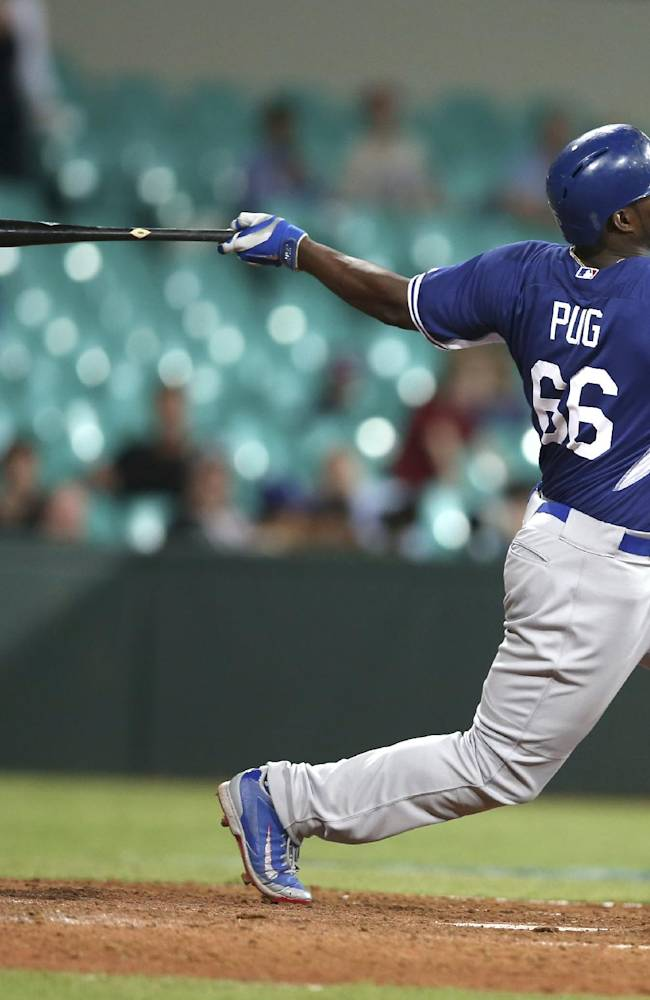 Los Angeles Dodgers' Yasiel Puig hits a two-run home run during their exhibition baseball game against Team Australia at the Sydney Cricket Gground in Sydney, Thursday, March 20, 2014. The Arizona Diamondbacks and the Dodgers open the Major League Baseball regular season with games on Saturday and Sunday