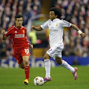 Real Madrid's Marcelo, right, is challenged by Liverpool's Philippe Coutinho during the Champions League group B soccer match between Liverpool and Real Madrid at Anfield Stadium, Liverpool, England, Wednesday Oct. 22, 2014