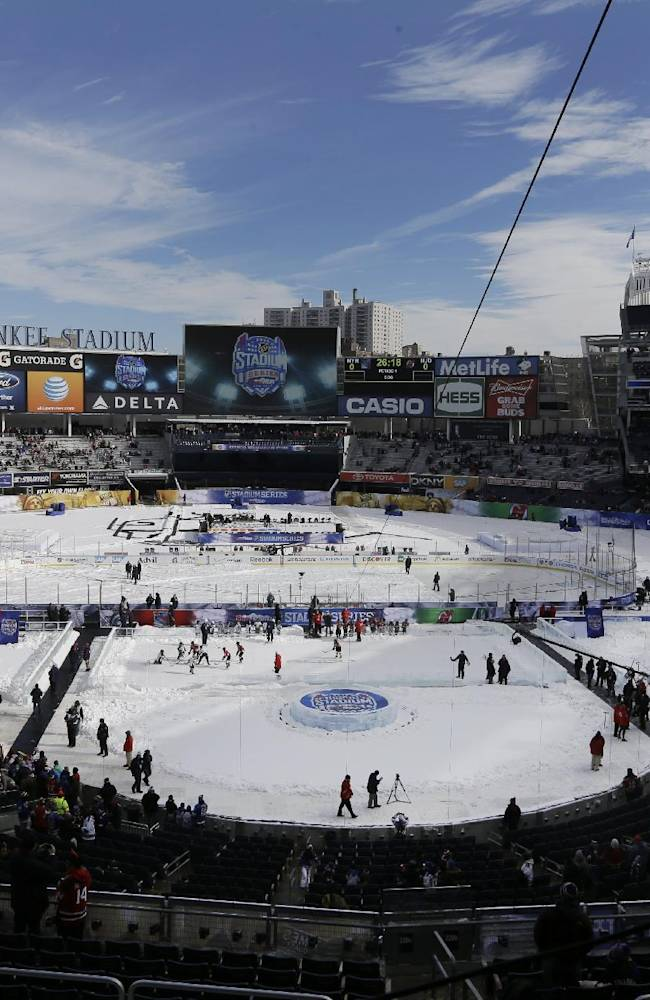 Fans wait for the start of an outdoor NHL hockey game between the New Jersey Devils and the New York Rangers Sunday, Jan. 26, 2014, at Yankee Stadium in New York