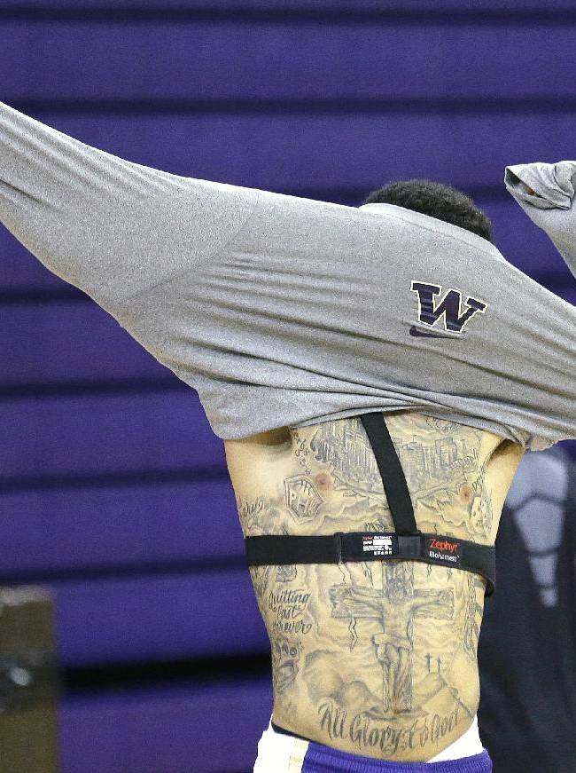 Washington's Nigel Williams-Goss puts on a shirt for basketball practice Tuesday, Oct. 8, 2013, in Seattle