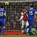 Arsenal's Aaron Ramsey, centre, has his shot on goal saved by Everton's goalkeeper Tim Howard, on ground, during the English Premier League soccer match between Arsenal and Everton at the Emirates Stadium in London, Sunday, Dec. 8, 2013