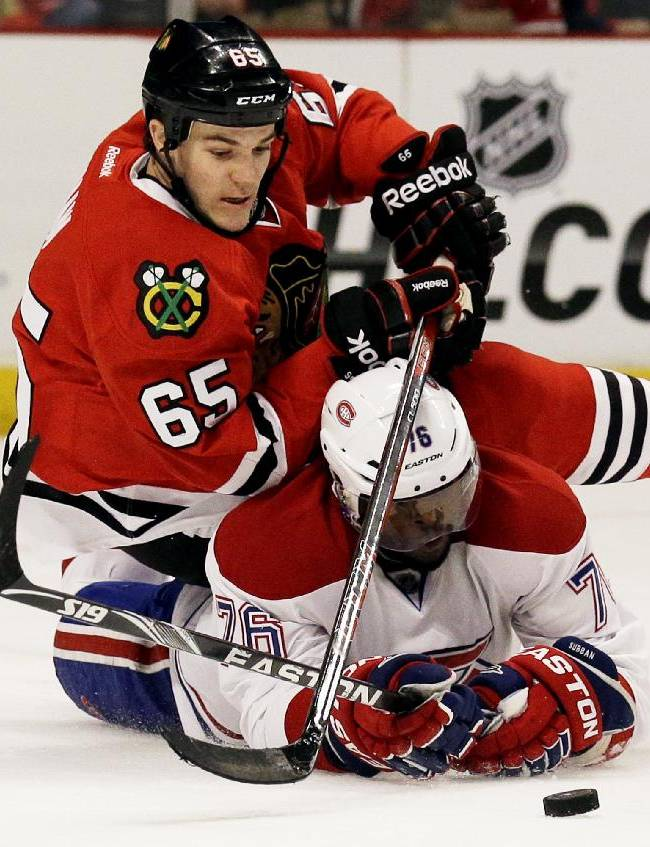 Chicago Blackhawks' Andrew Shaw (65), top, battles for the puck against Montreal Canadiens' P.K. Subban (76) during the second period of an NHL hockey game in Chicago, Wednesday, April 9, 2014