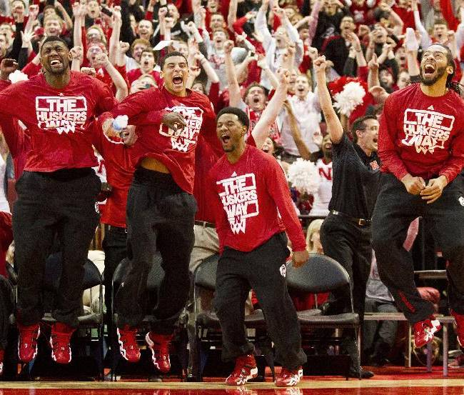 In this Sunday, March 16, 2014 photo, from left front standing, Nebraska players Leslee Smith, Tai Webster, Benny Parker and Terran Petteway react seconds after the NCAA Selection Show announced Nebraska's spot in the NCAA tournament bracket at a watch party in Lincoln, Neb