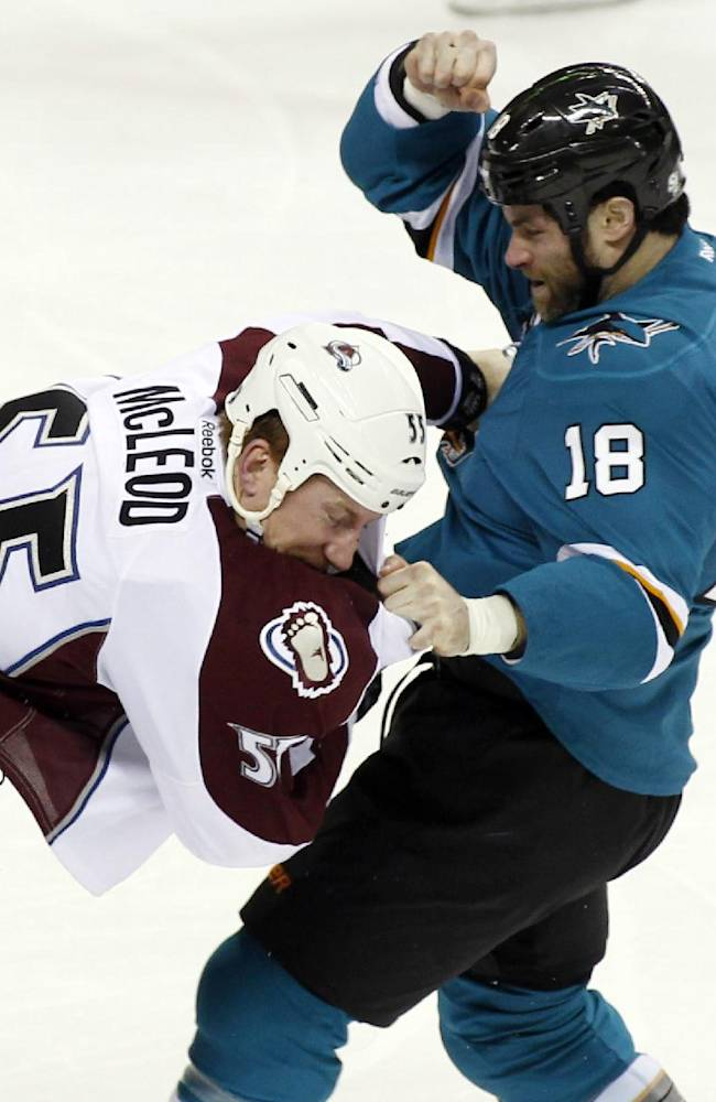San Jose Sharks' Mike Brown, right, fights with Colorado Avalanche's Cody McLeod during the first period of an NHL hockey game, Monday, Dec. 23, 2013, in San Jose, Calif
