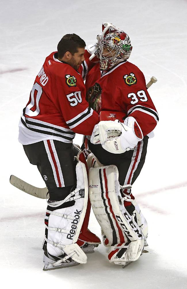Chicago Blackhawks goalie Corey Crawford hugs Nikolai Khabibulin, who was the winning goalie as the Blackhawks defeated the New York Islanders 3-2 in an NHL game in Chicago on Friday, Oct. 11, 2013