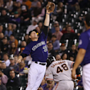 Colorado Rockies first baseman Justin Morneau, left, fields the throw as San Francisco Giants' Pablo Sandoval reaches first base on an infield single in the fourth inning of a baseball game in Denver on Monday, April 21, 2014 The Associated Press