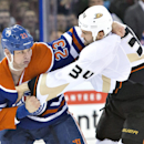 Anaheim Ducks' Daniel Winnik (34) fights with Edmonton Oilers' Matt Hendricks (23) during first-period NHL hockey game action in Edmonton, Alberta, Friday, March 28, 2014 The Associated Press