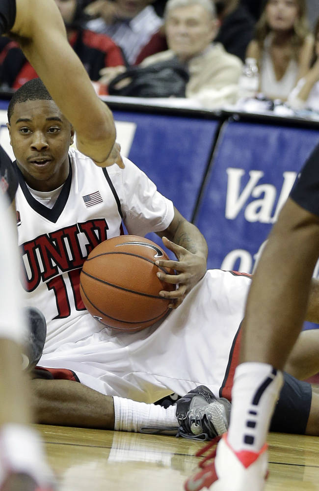 UNLV's Daquan Cook looks to pass the ball from the floor during the second half of an NCAA college basketball game against San Diego State on Wednesday, March 5, 2014, in Las Vegas. San Diego State defeated UNLV 73-64