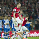 Arsenal's Thomas Vermaelen celebrates with teammates, at the end of their English FA Cup semifinal soccer match against Wigan Athletic, at the Wembley Stadium in London, Saturday, April 12, 2014
