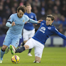 Everton's Muhamed Besic, right, fights for the ball against Manchester City's David Silva during the English Premier League soccer match between Everton and Manchester City at Goodison Park Stadium, Liverpool, England, Saturday Jan. 10, 2015