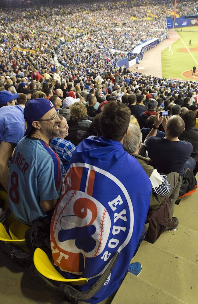 Fans wear Montreal Expos paraphernalia as they watch the Toronto Blue Jays in a pre-season baseball game against the New York Mets Friday, March 28, 2014 in Montreal