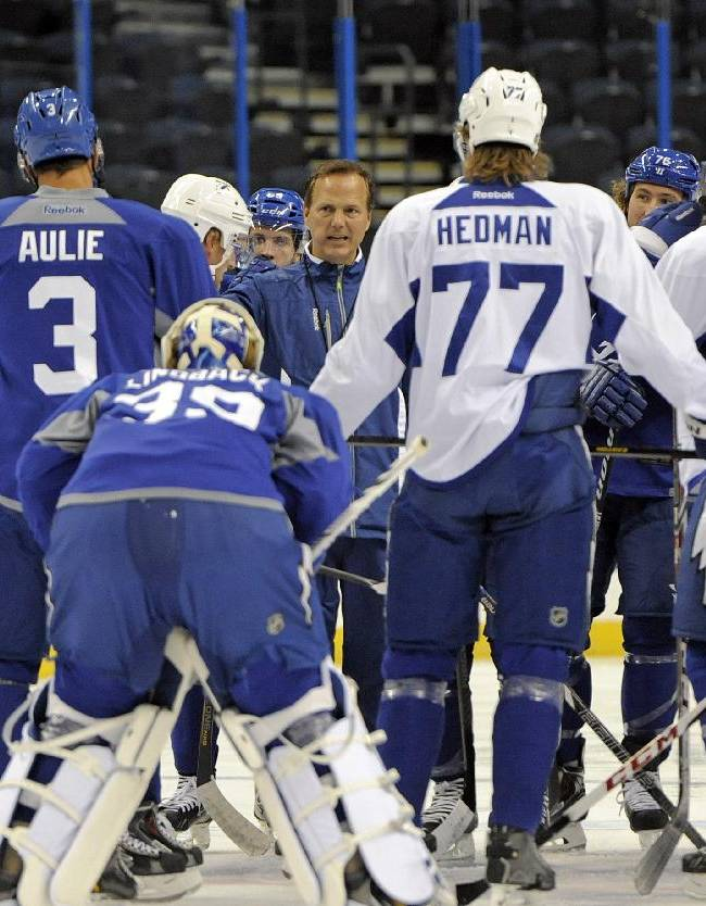 Tampa Bay Lightning head coach Jon Cooper, center, gathers his players on the ice for some instructions during NHL hockey camp Thursday, Sept. 12, 2013, in Tampa, Fla