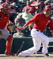 Los Angeles Angels' Carlos Pena, right, hits an RBI-single during the sixth inning of a spring exhibition baseball game against the Cincinnati Reds, Sunday, March 9, 2014, in Tempe, Ariz. (AP Photo/Morry Gash)