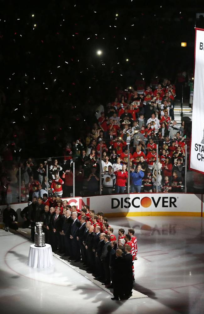 The Chicago Blackhawks stand with the Stanley Cup and the championship banner during ceremonies before an NHL hockey game between the Blackhawks and the Washington Capitals Tuesday, Oct. 1, 2013, in Chicago